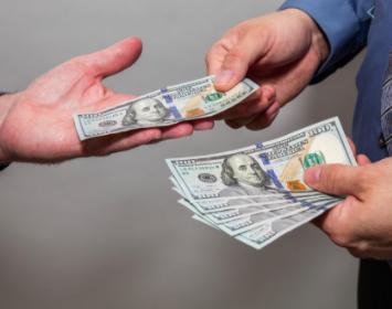 Someone handing someone else money