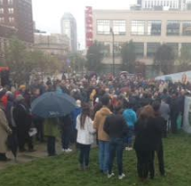 Lots of back of people on grassy lawn with buildings in the background, some holding umbrellas