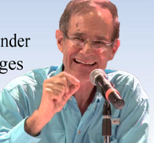 Older balding white man smiling and talking into a mic making a gesture with his hand