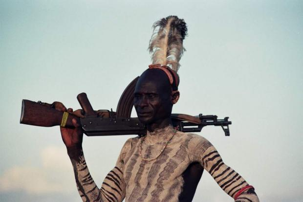 Photos of indigenous man with rifle