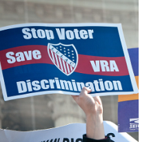 Red white and blue sign saying Stop Voter Discrimination Save VRA