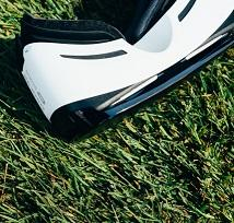 White and black virtual reality goggles laying on grass
