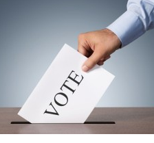 Man's hand putting a paper with the word VOTE on it into a slot in a box
