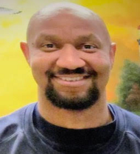 Bald black man with dark mustache and goatee, wearing blue shirt smiling