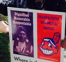 Poster with photo of Native American on left side and big cartoony smily Indian face that is Chief Wahoo the mascot of the Cleveland Indians