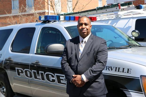 Black man standing next to police car