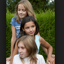Three young white girls with one above the other looking down