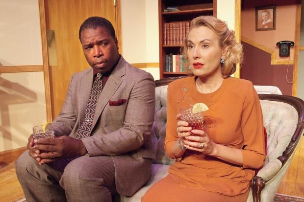 Black man and white woman sitting on a couch
