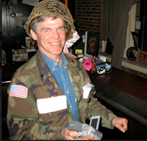 White man with a helmet on a big smile, and a camouflage jacket