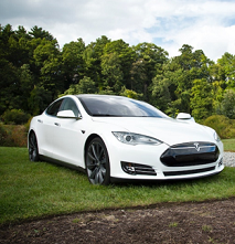 White sports car sitting outside on a green lawn with trees in the background