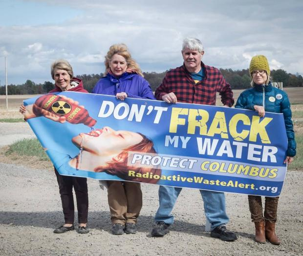 Four people holding a Don't Frack My Water sign