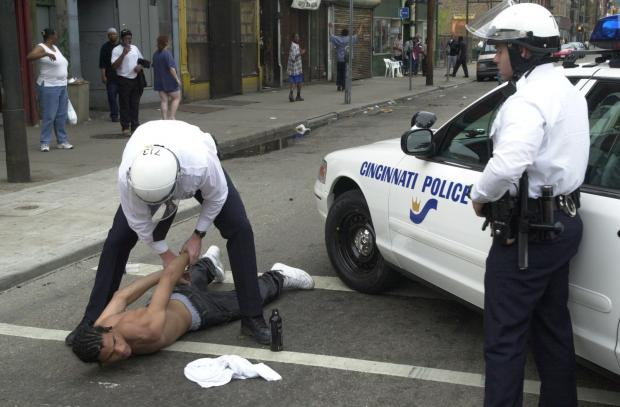 Two Cincinnati police with black man on ground in handcuffs