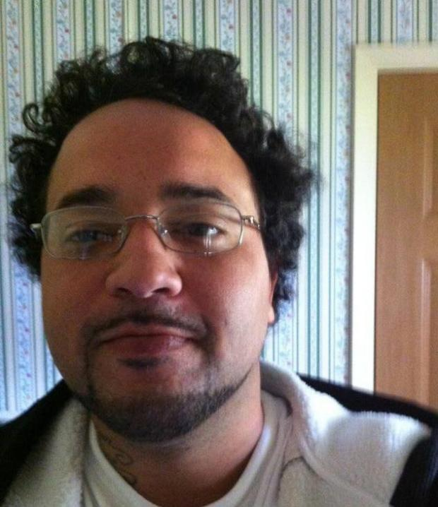Young man with wire rimmed glasses and goatee