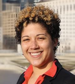 Head shot of young black woman with short curly hair smiling