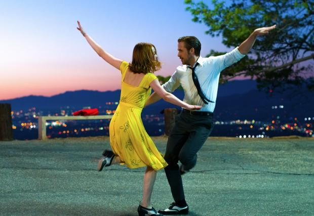 Woman in a yellow dress and man in a shirt and tie dancing wildly