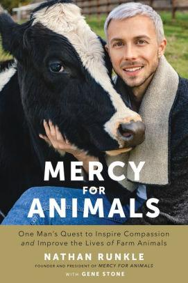 A man with white hair and goatee standing outside petting a black cow who has a white stripe up her nose and the word Mercy below