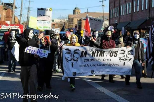 People marching wearing white and black Guy Fawkes masks carrying a long banner