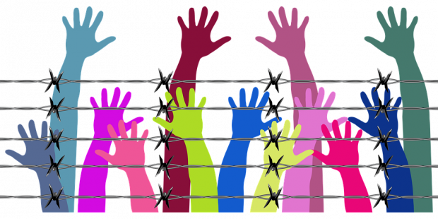 Different color arms and hands reaching up behind a barbed wire fence