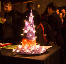 People at a party in the background and on a table in front a sparkly purple pointy hat with a wide brim and with an orange band around it