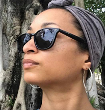 Young black woman with a scarf on her head and sunglasses looking left in front of a tree