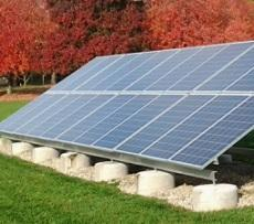 Big silver solar panel on ground sideways aimed at sky with red leaved trees in the background