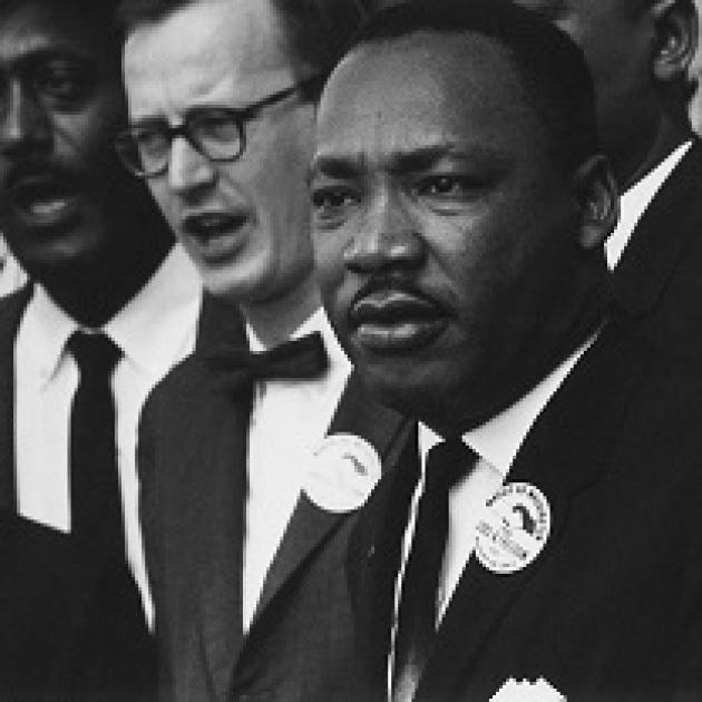 Black man in foreground, Martin Luther King Jr. surrounded by other men