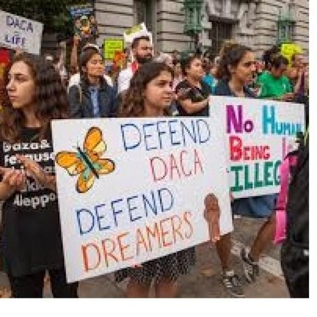 Young people with signs that say No Human Being is Illegal and Defend DACA, Defend Dreamers