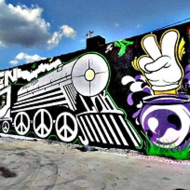 Mural with a train and peace signs for the wheels and a hand with two fingers up in a peace sign