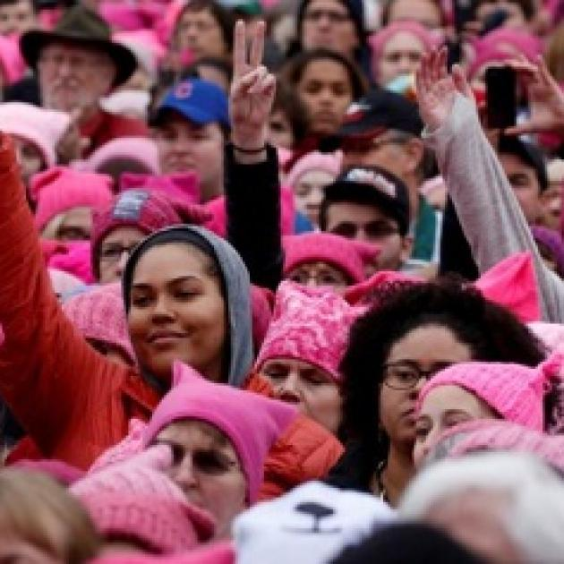 Lots of young women of different races wearing pink in a huge crowd with peace signs with their fingers in the air