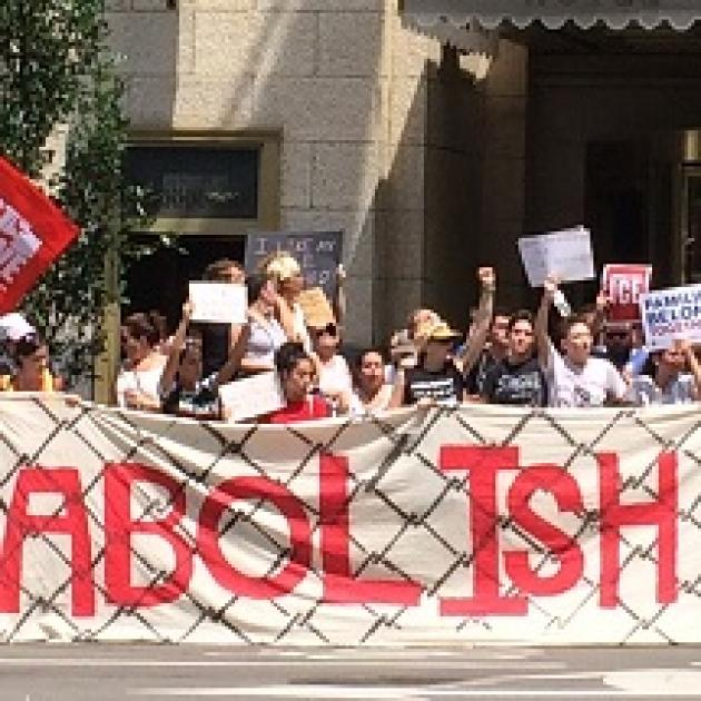 Words Abolish ICE real big on a sign behind people protesting