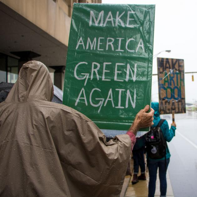 Person holding sign saying making American Green again