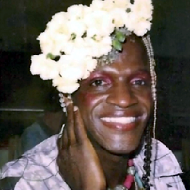 Photo of black woman smiling with her hand by her cheek and lots of white flowers in her hair