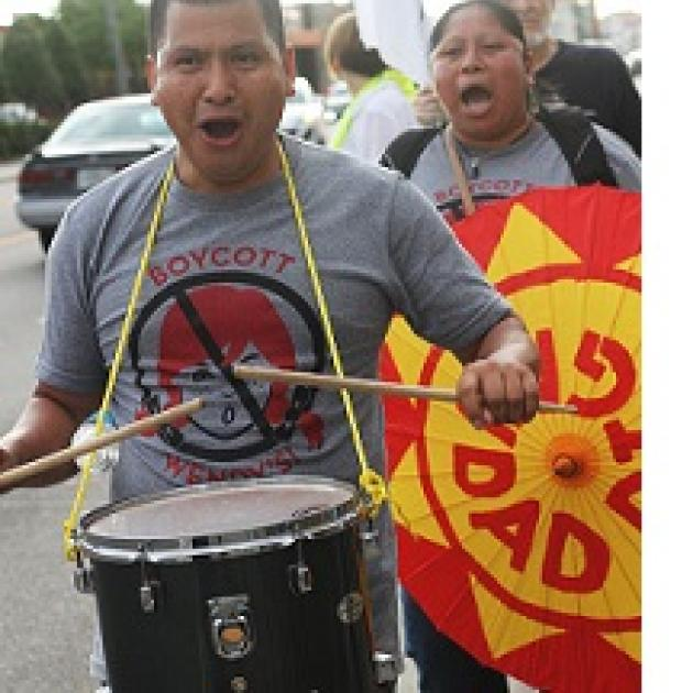 Latino man in foreground with drum around his neck and hitting it with drumsticks, his mouth open chanting, wearing a shirt that says Boycott Wendys with a picture of a girl's head with red pigtails and a No sign around it (circle with line through it) and a Latino woman behind him holding a bright orange and yellow sign also with her mouth open chanting
