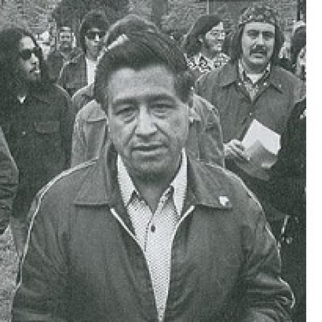 Black and white photo of Latino man wearing a jacket outside in front of a lot of other people