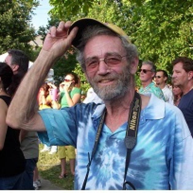 White man raising up his cap to the camera, smiling with sunglasses and gray mustache and beard, wearing a blue tye-dye t-shirt standing outside around trees and a lot of other people