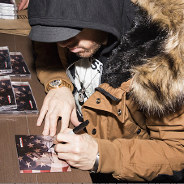 Guy in a black hoodie and brown heavy winter coat with fur collar sitting at a table with his face looking down where he is signing a CD