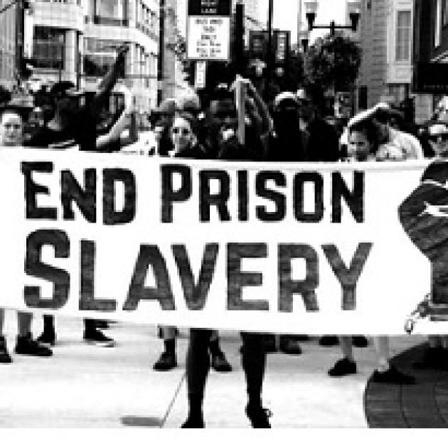 Black and white photo of people holding a sign outside in a protest that says End Prison Slavery