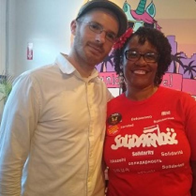 Young white man with facial hair, glasses and a hat posing with his arm around a black woman in a solidarity T-shirt