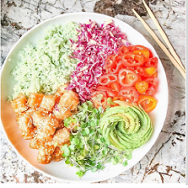 Plate of very brightly colorful food - green, purple, orange, red, yellow