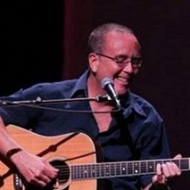 Balding white man with glasses wearing a blue button down shirt singing into a mic and playing a guitar