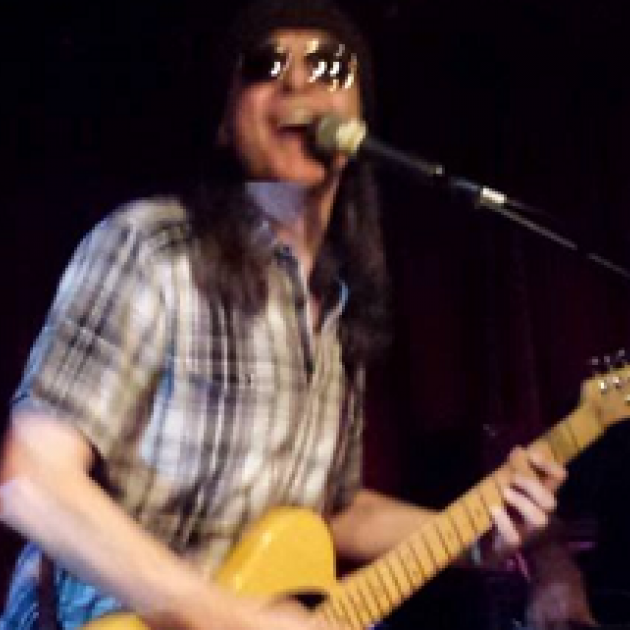 Man with long brown hair in plaid shirt playing a guitar and singing into a mic