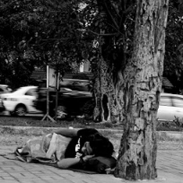 Black and white photo of person lying on the ground under a tree