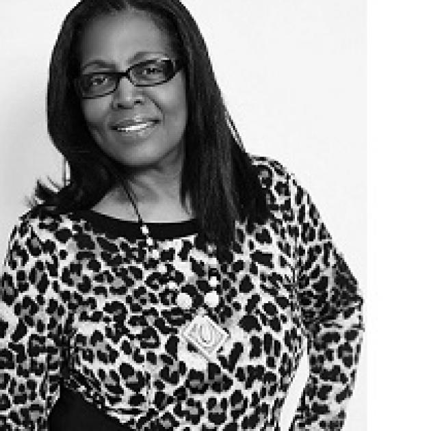Black and white photo of a black woman with shoulder length hair, black rimmed glasses, a leopard print top and a necklace