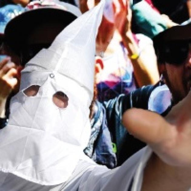 Klan member in pointy white mask holding his hand in the air