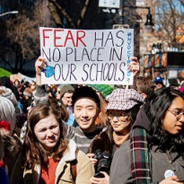 Young people wearing winter coats one young man holding a sign above his head that says Fear has no place in our schools