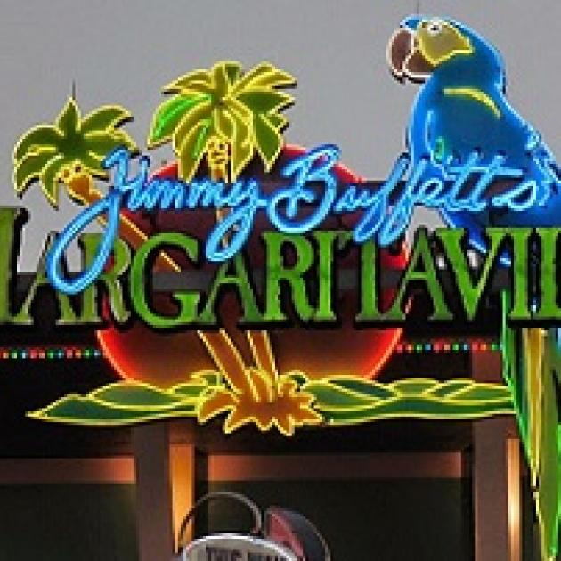 Neon sign with a parrot, palm trees, and the words in script Jimmy Buffet and the word in large capitals Margaritaville