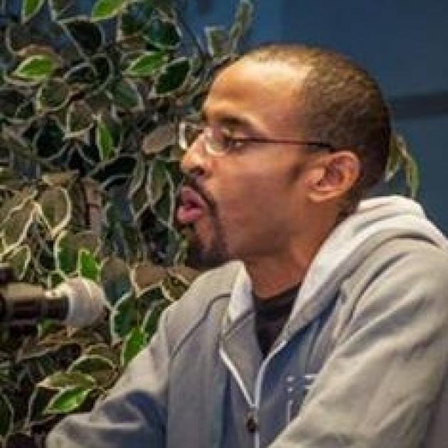 Young black man facing left talking into a microphone, he has short cropped hair and glasses and a goatee, sitting in front of a plant