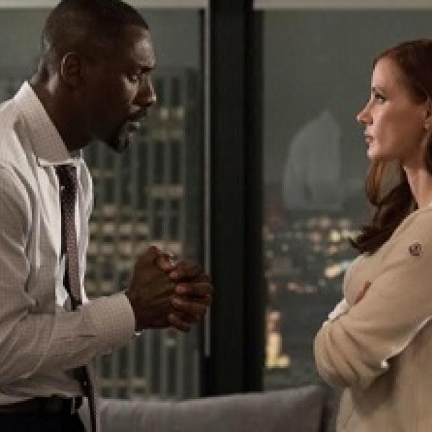 On the left a black man facing right in a white shirt and tie looking at a woman his hands in front of him with fingers clasped like he's praying and the white woman with long brown hair to the left is looking up at him with arms folded wearing a pick shirt. They are standing in front of a window looking over a nighttime city scene