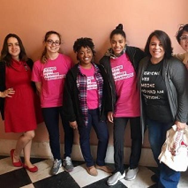 Young white and black women posing in a row with arms around each other smiling and wearing pink NARAL T-shirts