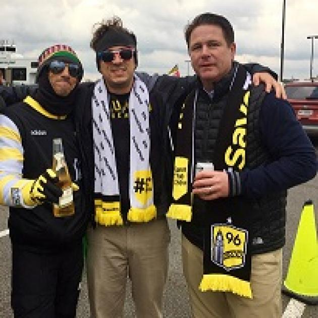 Three white guys wearing Save the Crew clothes smiling at the camera posing with their arms around each other